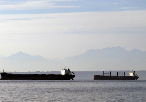 cargo ships waiting to be loaded with soybeans and corn at nearby Pier 86 are anchored in Elliott Bay, and in view of the Olympic mountains behind, in Seattle