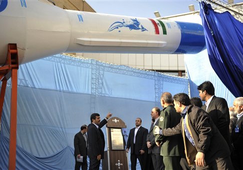 Former Iranian president Mahmoud Ahmadinejad gestures towards a model of Iran's new domestically-built light booster rocket Simorgh